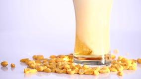 A cerveja está derramando no vidro no fundo branco com amendoins conservados filme