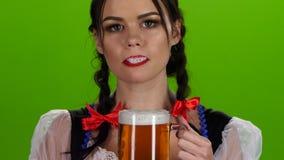 Cerveja flertando e bebendo da menina de Oktoberfest de um vidro Tela verde video estoque