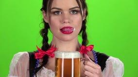 Cerveja flertando e bebendo da menina de Oktoberfest de um vidro Tela verde Movimento lento filme