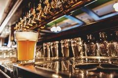 Cerveja fria no vidro que localiza na tabela Fotos de Stock Royalty Free