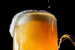 Cerveja grande vidro de transbordamento com espuma e bolhas isoladas Fotos de Stock