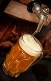A cerveja loura deliciosa do ofício encheu-se em um vidro da pinta na tabela de madeira fotos de stock royalty free