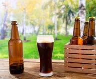 Cerveja no vidro, nas garrafas na tabela de madeira com o parque borrado da cidade no fundo, no alimento e no conceito da bebida, fotografia de stock