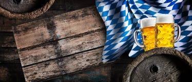 Cerveja pilsen dourada, tambores de cerveja e a bandeira bávara Fotografia de Stock