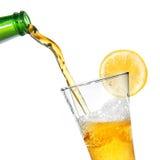 Cerveja que derrama da garrafa no vidro com limão fotografia de stock royalty free