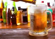 Cerveja que derrama na caneca Fotografia de Stock