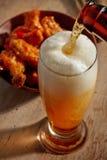 Cerveja que derrama no vidro Foto de Stock Royalty Free