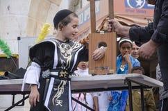 Cerveja-Sheva, ISRAEL - 5 de março de 2015: Menino judaico em um terno preto e pilha preta na fase com mágico - Purim Fotos de Stock Royalty Free