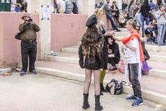 Cerveja-Sheva, ISRAEL - 5 de março de 2015: O homem com a câmara de vídeo dispara em povos em trajes do carnaval Menina no preto  Fotos de Stock