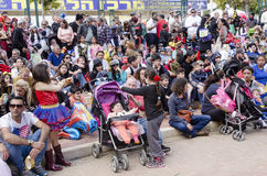Cerveja-Sheva, ISRAEL - 5 de março de 2015: Pais com audiência das crianças - sente e olhe o desempenho na rua - Purim Imagem de Stock Royalty Free