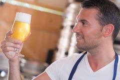 Cervejeiro considerável na cerveja uniforme do gosto na cervejaria imagem de stock royalty free