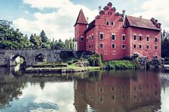 Cervena Lhota is a beautiful chateau in Czech. Republic. It stands at the middle of a lake on a rocky island. Travel destination. Mirrored architecture. Blue stock photos