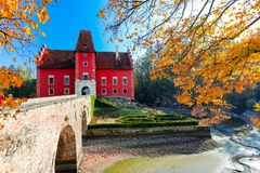 Cervena Lhota Castle in Czech Republic. Beautiful small red chateau Cervena Lhota, Castle in Czech Republic in autumn season with fall color and drained pond stock image