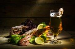 Cerveza con el camarón y las hierbas frescas Foto de archivo