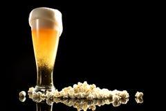 Cerveza con espuma y palomitas fotografía de archivo