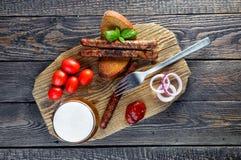 Cerveza con las salchichas, los tomates de cereza y la cebolla, visión superior Foto de archivo