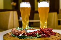 Cerveza con las salchichas y las costillas de cerdo asadas a la parrilla Fotografía de archivo libre de regalías