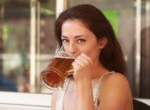 Cerveza de cerveza dorada de consumición de la mujer feliz hermosa Foto de archivo