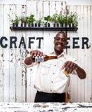 Cerveza de colada del camarero en el vidrio fotografía de archivo libre de regalías