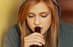 Cerveza de consumición de la mujer adolescente y cigarrillo que fuma Imágenes de archivo libres de regalías