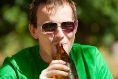 Cerveza de consumición del hombre de la botella fotografía de archivo libre de regalías