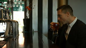 Cerveza de consumición del hombre de negocios hermoso en el contador metrajes