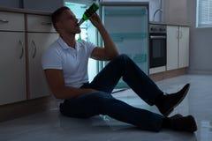 Cerveza de consumición del hombre en cocina Fotografía de archivo libre de regalías