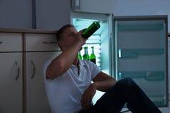 Cerveza de consumición del hombre en cocina Fotos de archivo