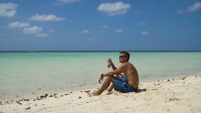 Cerveza de consumición del hombre en la playa almacen de metraje de vídeo