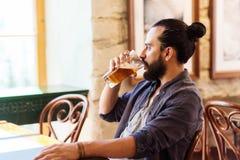 Cerveza de consumición del hombre feliz en la barra o el pub imagen de archivo libre de regalías