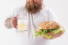 Cerveza de consumición del hombre gordo feliz con el bocadillo Imagenes de archivo