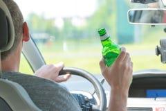 Cerveza de consumición del hombre mientras que conduce un coche Fotos de archivo libres de regalías
