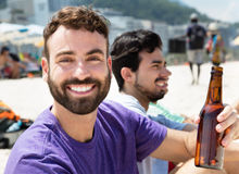 Cerveza de consumición del individuo caucásico con los amigos en la playa Fotografía de archivo libre de regalías