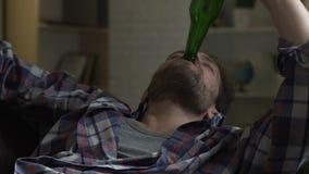 Cerveza de consumición del individuo de la botella y sofá dormido que cae, alcoholismo y malos hábitos almacen de video