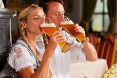 Cerveza de consumición del trigo de los pares bávaros fotografía de archivo