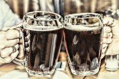Cerveza de consumición en el pub Vidrios de cerveza en manos Fotos de archivo libres de regalías
