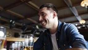 Cerveza de consumición feliz del hombre joven en la barra o el pub almacen de metraje de vídeo