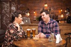 Cerveza de consumici?n de los pares jovenes y alegres y tener un buen rato imágenes de archivo libres de regalías