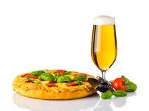 Cerveza de cristal con la rueda de la pizza y del cortador fotografía de archivo