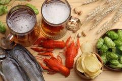 Cerveza de cristal con los cangrejos, los conos de salto y los oídos del trigo en fondo de madera ligero Concepto de la cervecerí fotos de archivo