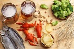 Cerveza de cristal con los cangrejos, los conos de salto y los oídos del trigo en fondo de madera ligero Concepto de la cervecerí imagen de archivo