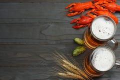 Cerveza de cristal con los cangrejos, los conos de salto y los oídos del trigo en fondo de madera oscuro Concepto de la cervecerí fotos de archivo