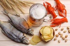 Cerveza de cristal con los cangrejos y pescados secados en fondo de madera ligero Concepto de la cervecería de la cerveza Fondo d foto de archivo libre de regalías