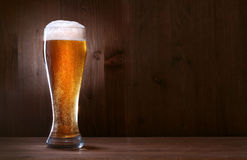 Cerveza de cristal en el fondo de madera foto de archivo