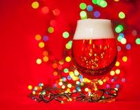 Cerveza de la Navidad con las luces en rojo Fotografía de archivo