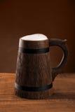 Cerveza de la taza con un casquillo de la espuma en un fondo oscuro Fotos de archivo