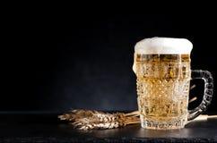 Cerveza de la taza en un fondo negro foto de archivo