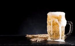 Cerveza de la taza en un fondo negro imagen de archivo