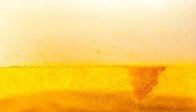 Cerveza de oro con espuma Foto de archivo libre de regalías
