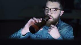 Cerveza del hombre y PC de consumición con almacen de metraje de vídeo